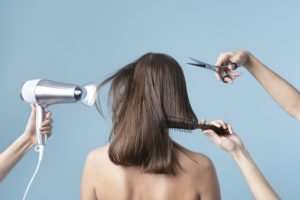 a womans hair is being cut and blow dried in a studio with blue background