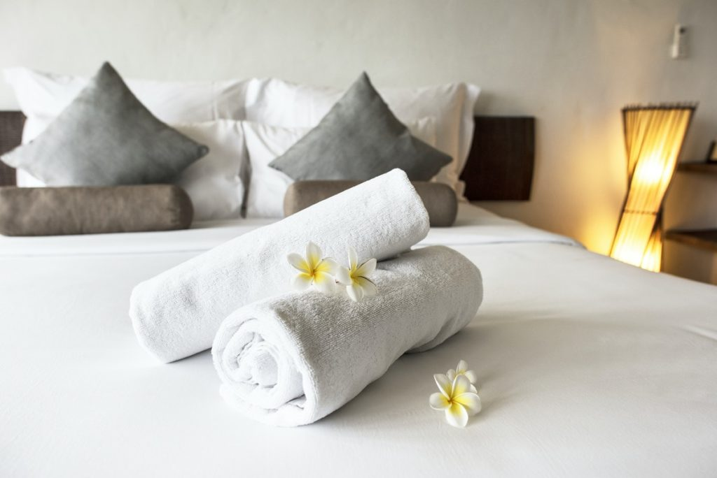 rolled up towels on a hotel bed
