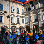 grads throw their hats in the air in vilnus university to celebrate
